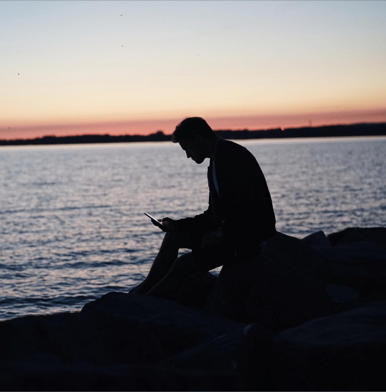 homme regardant son téléphone au bord de la mer